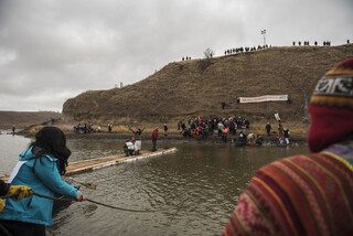 Police wait on top of Turtle Island on Thanksgiving Day as water protectors travel across first with canoes and then with their rudimentary bridge.